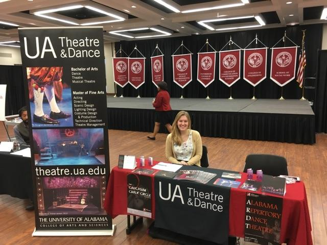 a student sitting at a table advertising the department's programs