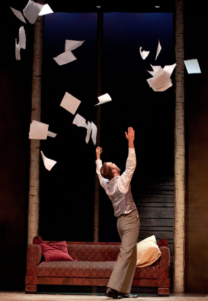 an actor onstage tossing a sheaf of papers in the air