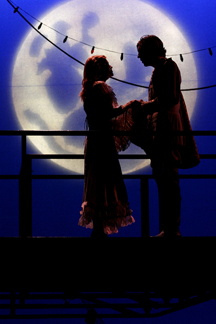 a man and a woman standing backlit against a full moon