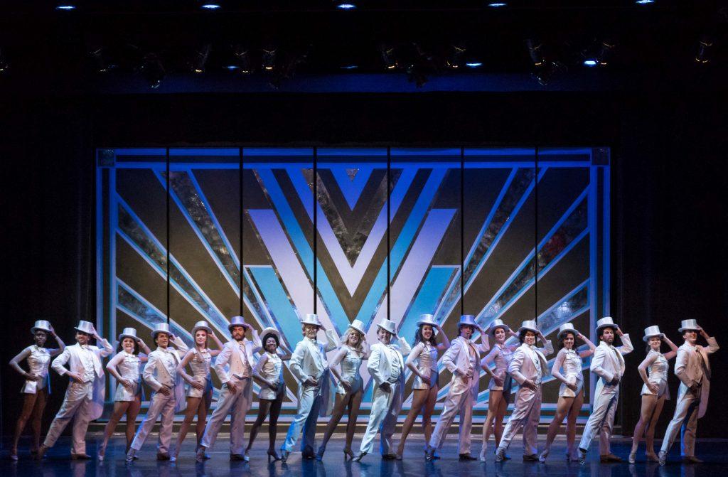 cast members dancing against an art deco backdrop