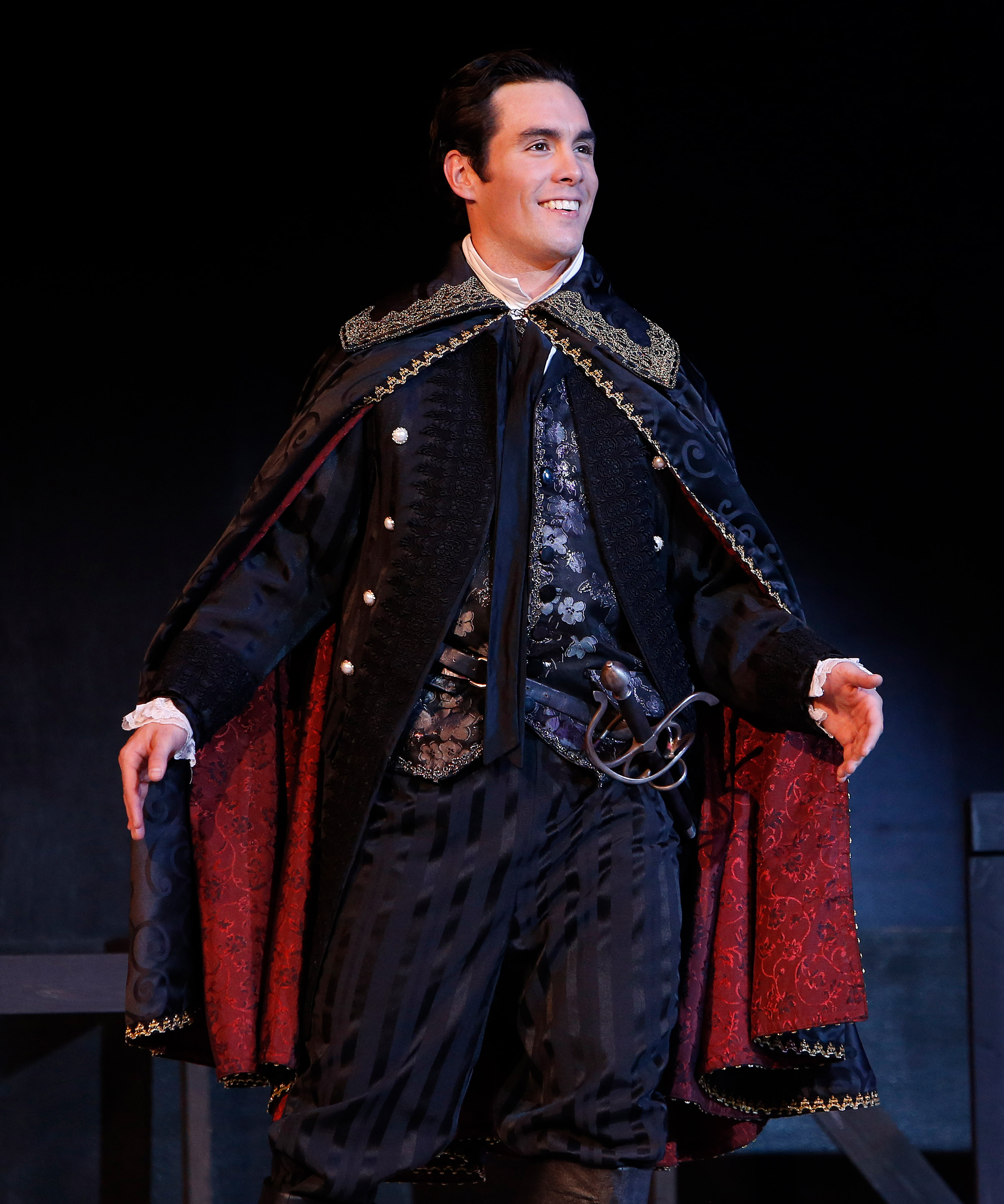smiling male actor in period attire